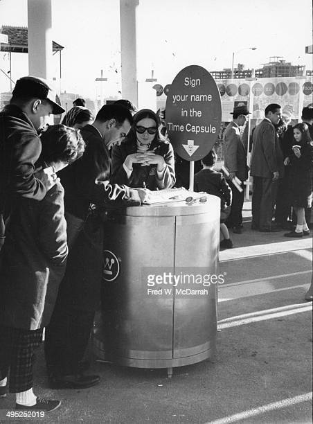 Attendees sign their names to be included in a time capsule at the 1964 New York World's Fair Flushing Medows New York New York mid 1960s