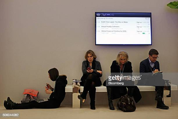 Attendees sit and use mobile devices between sessions in the Congress Center during the World Economic Forum in Davos Switzerland on Thursday Jan 21...