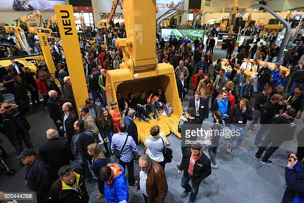 Attendees sit in a excavator bucket on the Caterpillar Inc exhibition stand during the Bauma construction industry fair in Munich Germany on Monday...