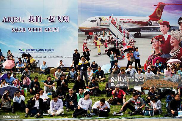 Attendees sit in front of an advertisement for the Commercial Aircraft Corp of China ARJ21 jet during the China International Aviation Aerospace...
