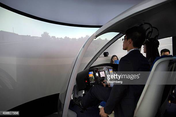 Attendees sit inside an Aviation Industry Corp of China flight training device for the AC311 helicopter during the China International Aviation...