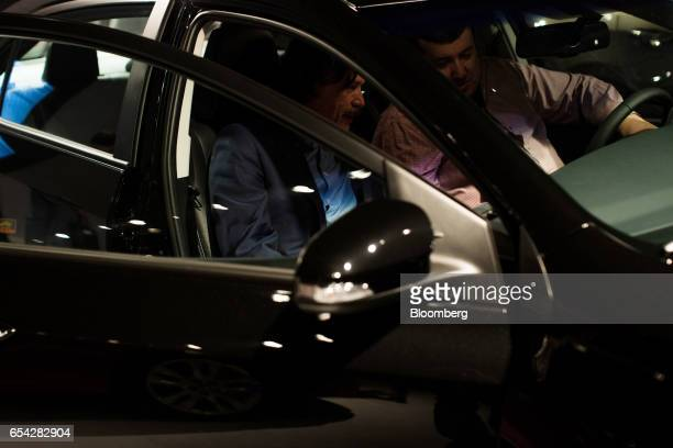 Attendees sit inside the new2018 Toyota Motor Corp. Corolla vehicle during the company's launch event in Sao Paulo, Brazil, on Thursday, March 16,...