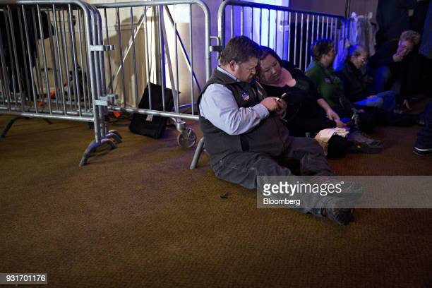 Attendees sit on the floor during an election night rally with Conor Lamb Democratic candidate for the US House of Representatives not pictured in...