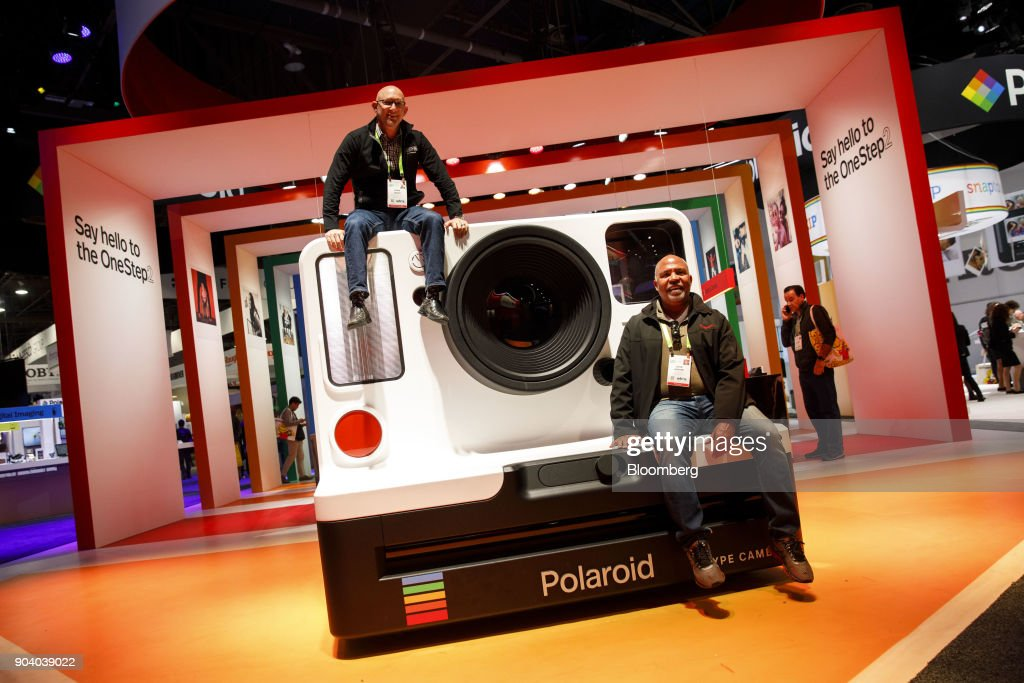 Attendees sit on top of a model of a Impossible BV Polaroid Original OneStep 2 polaroid camera at the 2018 Consumer Electronics Show (CES) in Las Vegas, Nevada, U.S., on Thursday, Jan. 11, 2018. Electric and driverless cars will remain a big part of this year's CES, as makers of high-tech cameras, batteries, and AI software vie to climb into automakers' dashboards. Photographer: Patrick T. Fallon/Bloomberg via Getty Images
