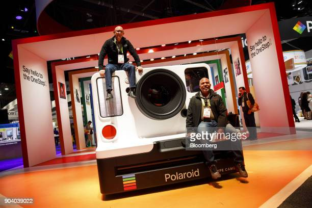 Attendees sit on top of a model of a Impossible BV Polaroid Original OneStep 2 polaroid camera at the 2018 Consumer Electronics Show in Las Vegas...