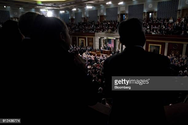 Attendees stand and clap as US President Donald Trump center pauses while delivering a State of the Union address to a joint session of Congress at...