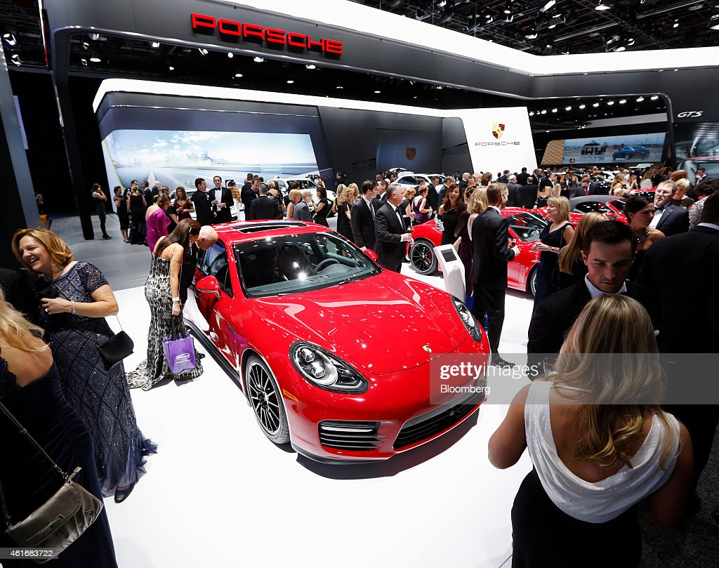 Attendees stand around the Porsche AG exhibit at the Charity Preview for North American International Auto Show (NAIAS) in Detroit, Michigan, U.S., on Friday, Jan. 16, 2015. Since 1976, the Charity Preview has raised more than $100 million for Southeastern Michigan children's charities. Photographer: Jeff Kowalsky/Bloomberg via Getty Images