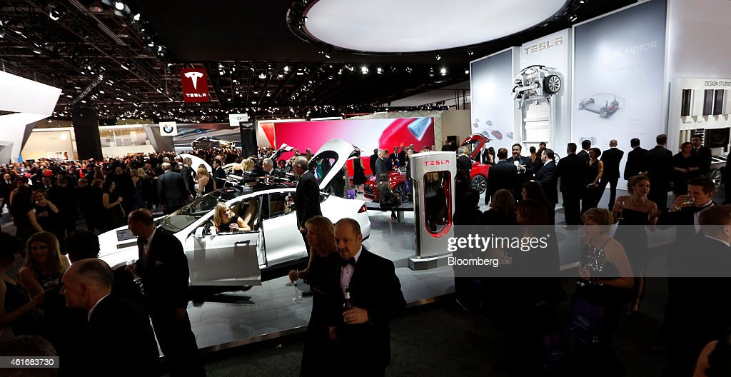 Attendees stand around the Tesla Motors Inc. exhibit at the Charity Preview for North American International Auto Show (NAIAS) in Detroit, Michigan, U.S., on Friday, Jan. 16, 2015. Since 1976, the Charity Preview has raised more than $100 million for Southeastern Michigan children's charities. Photographer: Jeff Kowalsky/Bloomberg via Getty Images
