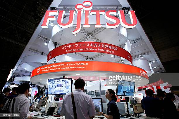 Attendees stand at the Fujitsu Ltd booth at the CEATEC Japan 2013 exhibition in Chiba City Japan on Tuesday Oct 1 2013 CEATEC an information...