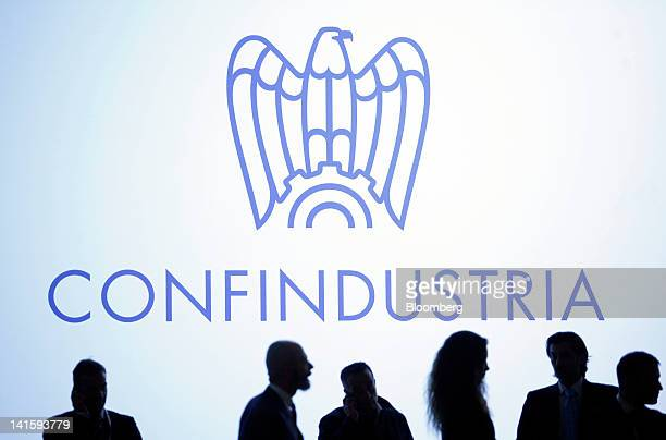 Attendees stand beneath a logo of Italy's employers' association Confindustria, during the 'Reforms For Growth' conference in Milan, Italy, on...