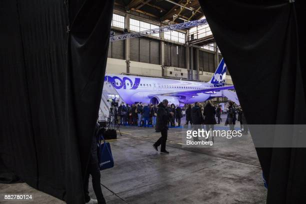 Attendees stand beside an Airbus SE A320 narrowbody jet operated by Joon Air FranceKLM Group's new lowcost carrier in a hangar at Charles de Gaulle...
