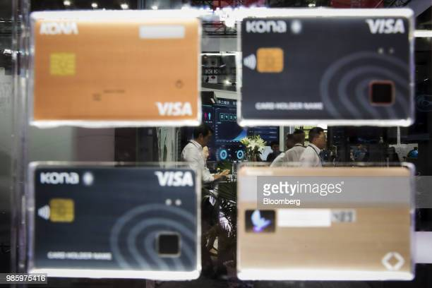 Attendees stand beyond a display of Visa Inc biometric credit cards manufactured by Kona I Co at the Mobile World Congress Shanghai in Shanghai China...