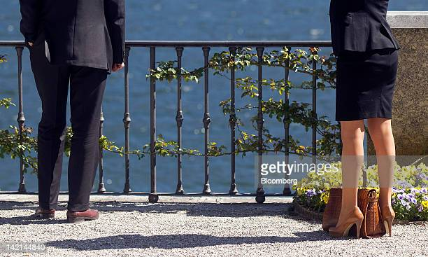 Attendees stand by Lake Como during a break in sessions at the Ambrosetti Workshop in Cernobbio, near Como, Italy, on Friday, March 30, 2012. The two...