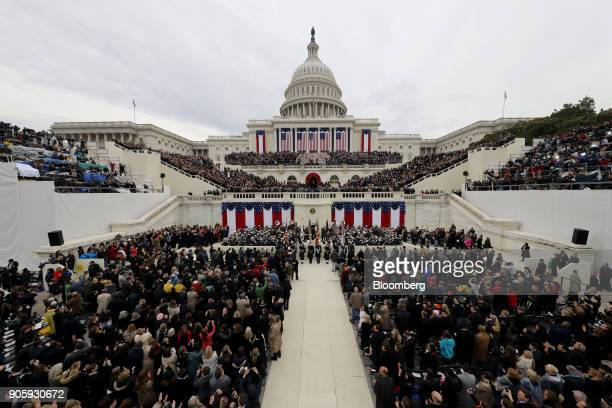 Attendees stand during the 58th presidential inauguration in Washington DC US on Friday Jan 20 2017 The one year anniversary of US President Donald...
