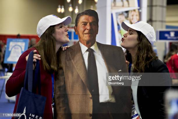 Attendees stand for a photograph with a cardboard cutout depicting former President Ronald Reagan during the Conservative Political Action Conference...