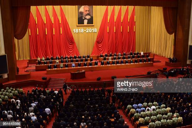 Attendees stand for The Internationale during the ceremony to mark German philosopher Karl Marx's 200th birth anniversary at the Great Hall of the...