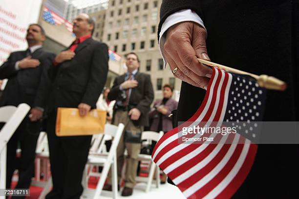 Attendees stand for the Pledge of Allegiance during a swearingin ceremony for new US citizens October 26 2004 in New York City In recognition of...