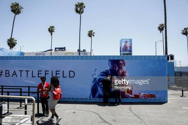 Attendees stand in front of signage for the Battlefield V video game during an Electronic Arts Inc Play event ahead of the E3 Electronic...