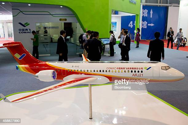 Attendees stand near a model Commercial Aircraft Corp of China ARJ21 aircraft during the China International Aviation Aerospace Exhibition in Zhuhai...