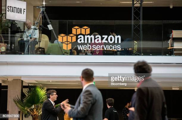Attendees stand near Amazoncom Inc Web Services signage during the Station F startup campus launch party in Paris France on Thursday June 29 2017 One...