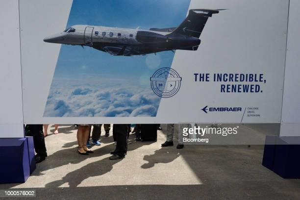 Attendees stand near an advertisement for Embraer SA on day two of the Farnborough International Airshow 2018 in Farnborough UK on Tuesday July 17...