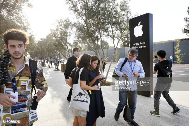 Attendees stand near Apple Inc signage ahead of an event at the Steve Jobs Theater in Cupertino California US on Tuesday Sept 12 2017 Apple plans to...