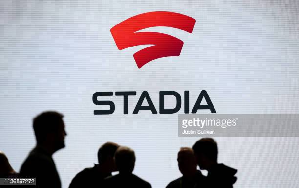 Attendees stand near the Stadia logo during the GDC Game Developers Conference on March 19 2019 in San Francisco California Google announced Stadia a...