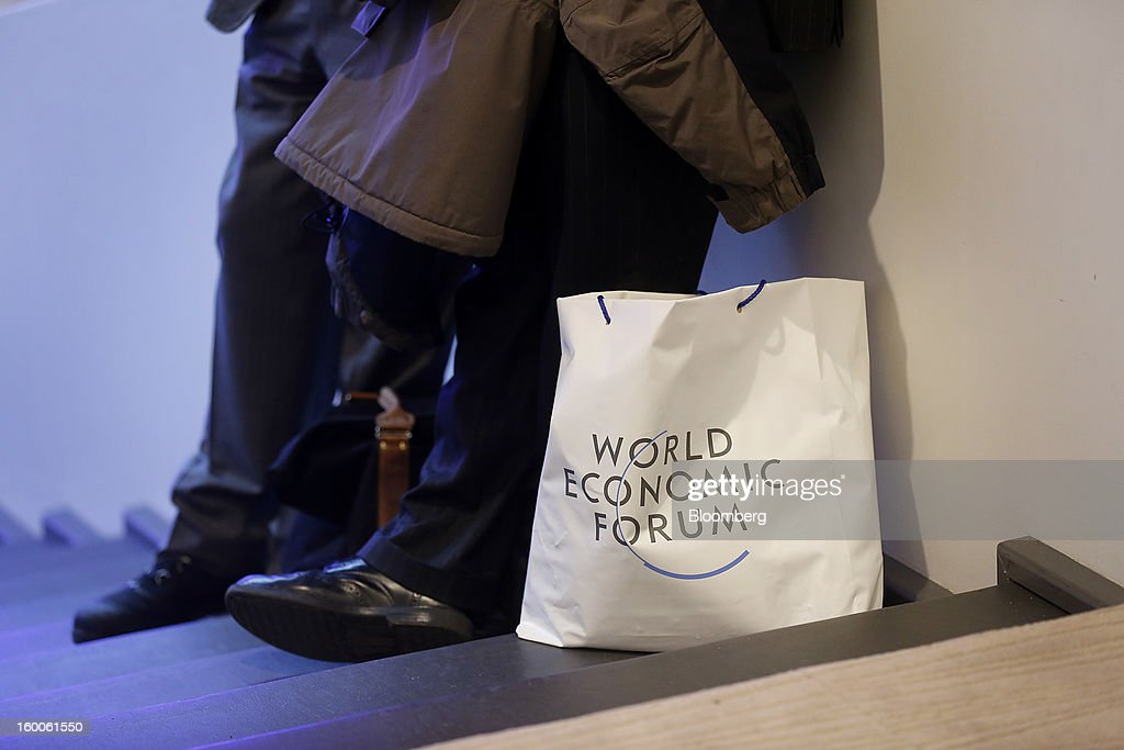 Attendees stand next to a World Economic Forum (WEF) bag inside the Congress Center on day three in Davos, Switzerland, on Friday, Jan. 25, 2013. World leaders, influential executives, bankers and policy makers attend the 43rd annual meeting of the World Economic Forum in Davos, the five day event runs from Jan. 23-27. Photographer: Simon Dawson/Bloomberg via Getty Images