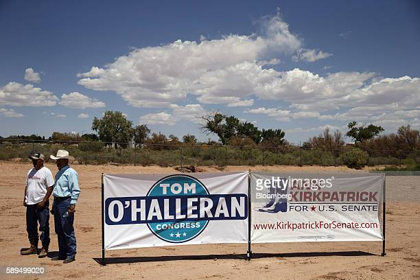 Attendees stand next to campaign signs for Tom O'Halleran a Democrat from Arizona currently running for Arizona's 1st congressional district and...