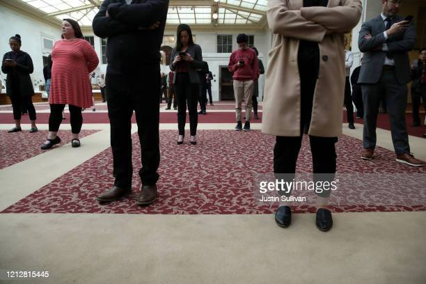 Attendees stand with space between themselves as San Francisco Mayor London Breed speaks during a press conference at San Francisco City Hall on...