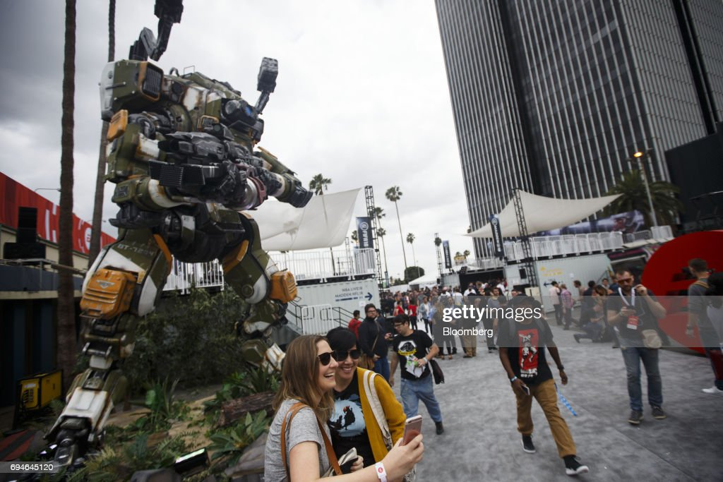 Attendees take a selfie photograph with a Titan from the video game 'Titanfall' outside of the Electronic Arts Inc. (EA) Play event ahead of the E3 Electronic Entertainment Expo in Los Angeles, California, U.S., on Saturday, June 10, 2017. EA revealed two new titles along with the annual iterations of the company's sports games, as well as unveiling the highly anticipated 'Star Wars: Battlefront II' open-world multiplayer gameplay. Photographer: Patrick T. Fallon/Bloomberg via Getty Images