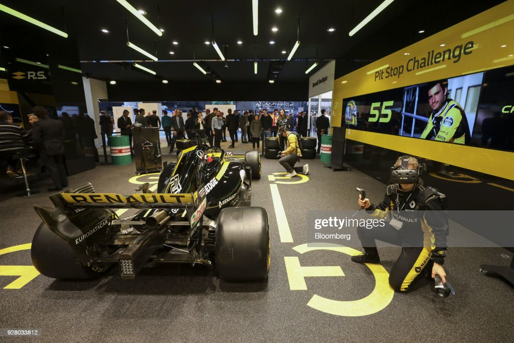 Attendees take part in a virtual reality Formula One tire change experience beside a racing car on the Renault SA stand on the opening day of the 88th Geneva International Motor Show in Geneva, Switzerland, on Tuesday, March 6, 2018. The show opens to the public on March 8, and will showcase the latest models from the world's top automakers. Photographer: Chris Ratcliffe/Bloomberg via Getty Images