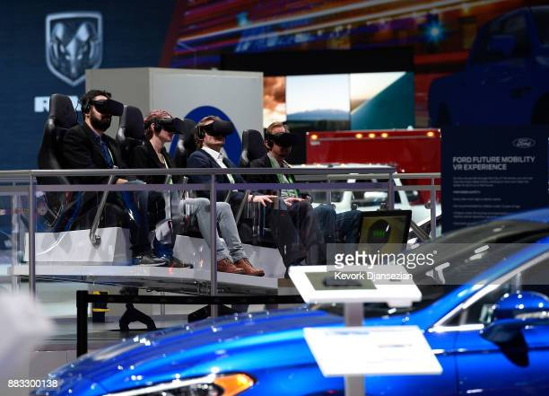 Attendees take part in a virtual reality ride in the Ford booth during the auto trade show AutoMobility LA at the Los Angeles Convention Center...