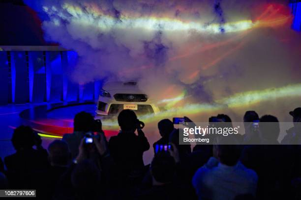 Attendees take photographs as the Subaru Corp. STI S209 vehicle is revealed during the 2019 North American International Auto Show in Detroit,...
