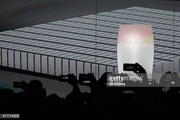 Attendees take photographs during the unveiling of Tesla Motors Inc's 'Powerwall' at an event in Hawthorne California US on Thursday April 30 2015...