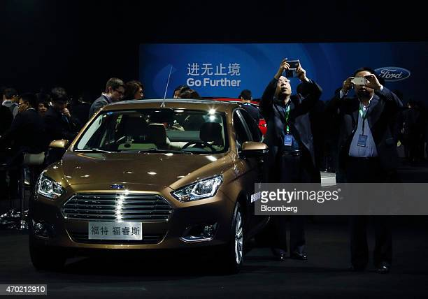 Attendees take photographs next to a Ford Motor Co Fusion vehicle displayed at a media event ahead of the 16th Shanghai International Automobile...