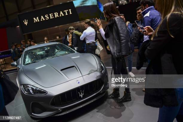 Attendees take photographs of a Maserati SpA GranTurismo MC automobile ahead of the 89th Geneva International Motor Show in Geneva Switzerland on...
