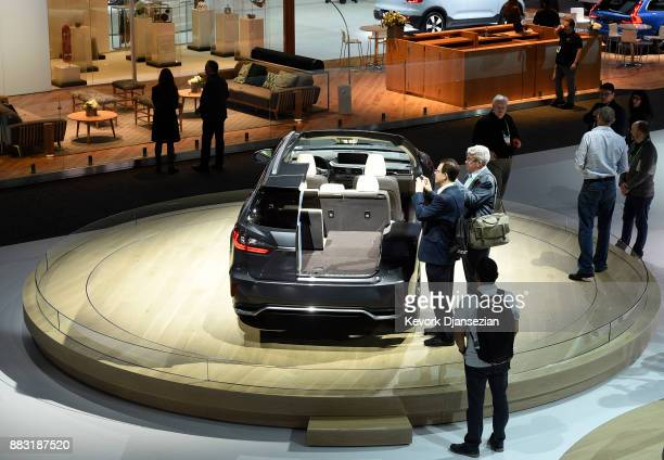 Attendees take photographs of cutaway model of the 2018 Lexus RX 350L showing the interior during the auto trade show AutoMobility LA at the Los...