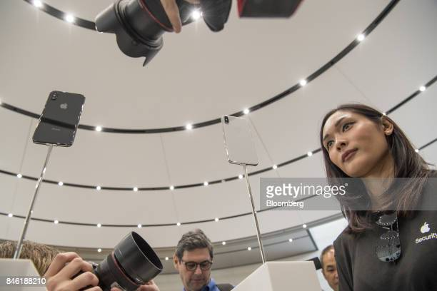 Attendees take photographs of the Apple Inc iPhone X during an event at the Steve Jobs Theater in Cupertino California US on Tuesday Sept 12 2017...