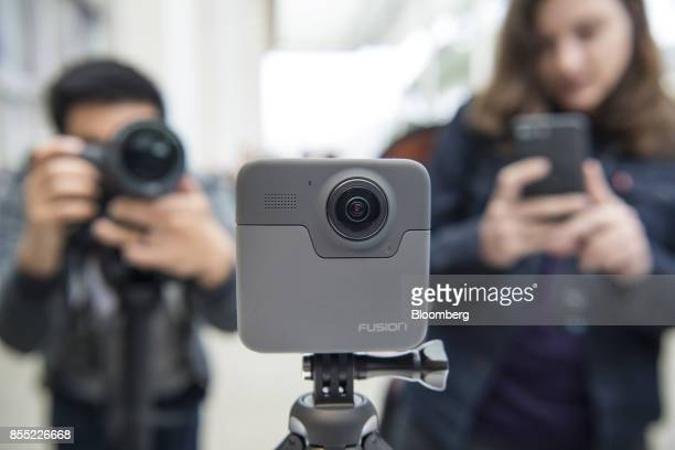 Attendees take photographs of the GoPro Inc Fusion 360 camera during an event in San Francisco California US on Thursday Sept 28 2017 GoPro unveiled...