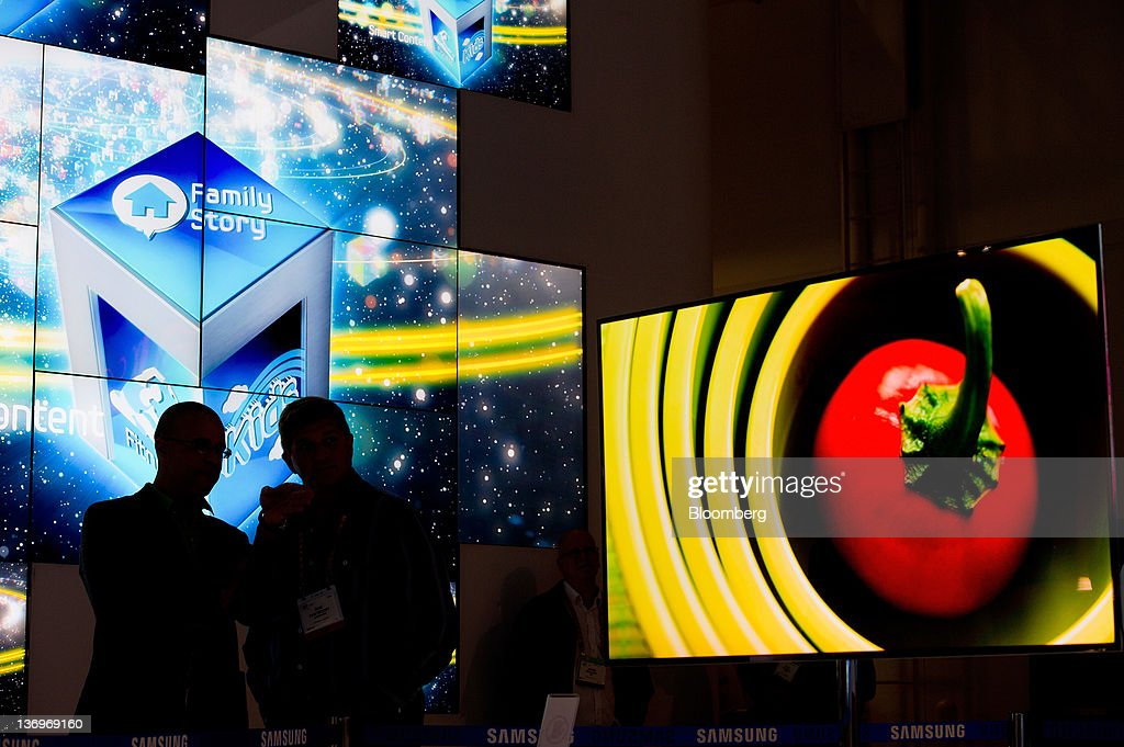 Attendees take photographs of the new Samsung Electronics Co. OLED television displayed at the International Consumer Electronics Show (CES) in Las Vegas, Nevada, U.S., on Friday, Jan. 13, 2012. The 2012 CES trade show, which runs through Jan 13, features more than 2,700 global technology companies presenting consumer tech products and is expected to draw over 140,000 attendees. Photographer: David Paul Morris/Bloomberg via Getty Images
