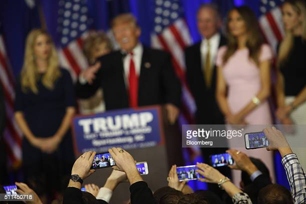Attendees take photographs using smartphones as Donald Trump president and chief executive of Trump Organization Inc and 2016 Republican Presidential...