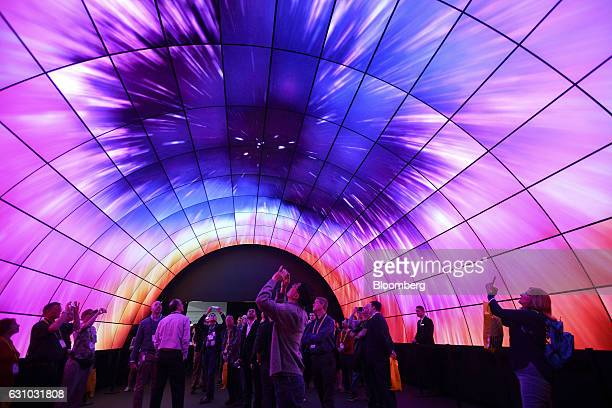 Attendees take photographs with mobile devices while standing under a tunnel wall of LG OLED 4K TVs during the 2017 Consumer Electronics Show in Las...