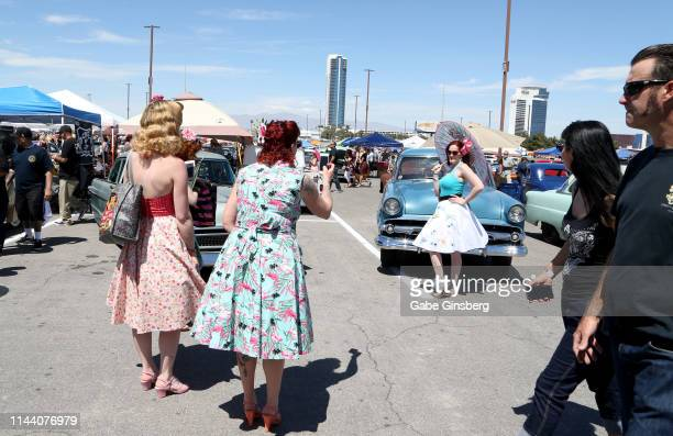 Attendees take photos in front of classic cars during the Viva Las Vegas Rockabilly Weekend's car show at the Orleans Arena on April 20 2019 in Las...