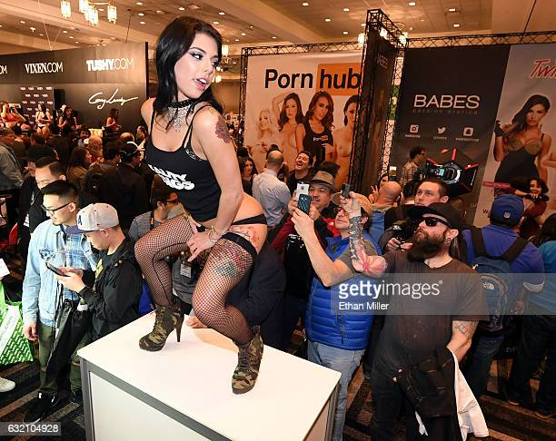 Attendees take photos of adult film actress Gina Valentina at the Reality Kings booth at the 2017 AVN Adult Entertainment Expo at the Hard Rock Hotel...