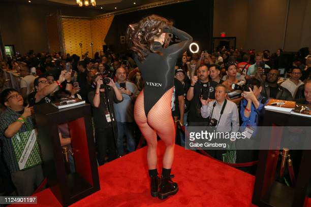 Attendees take photos of adult film actress Tori Black dancing in Lansky's Blacked Tushy and Vixen adult studios booth at the 2019 AVN Adult...