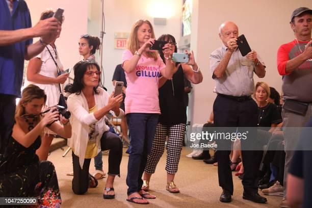 Attendees take photos of Florida Democratic gubernatorial nominee Andrew Gillum former New York City Mayor Michael Bloomberg and US Rep Debbie...
