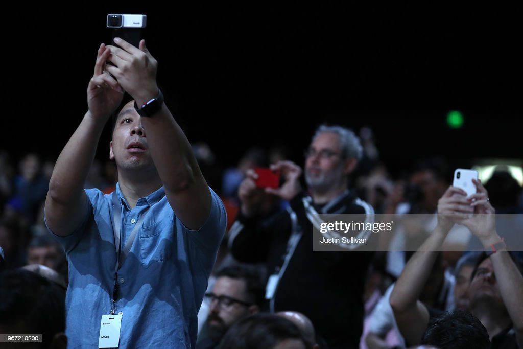 Attendees take pictures before the start of the opening keynote during the 2018 Apple Worldwide Developer Conference (WWDC) at the San Jose Convention Center on June 4, 2018 in San Jose, California. Apple CEO Tim Cook will kick off the WWDC that runs through June 8.