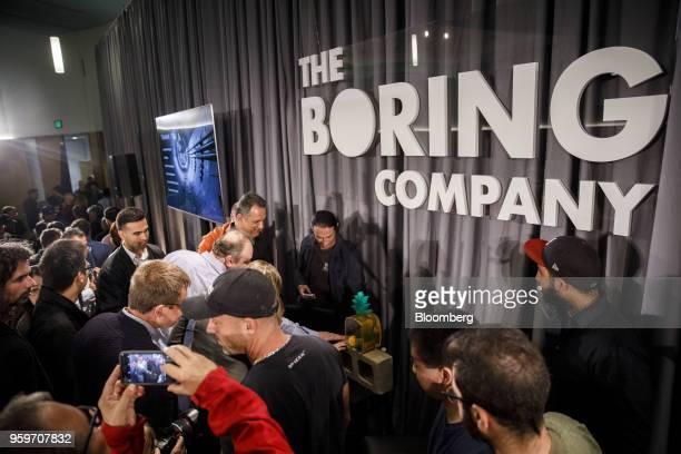"""Attendees take pictures of """"Gary,"""" a pet snail, perched atop a brick made from dirt removed by a tunnel boring machine during a Boring Co. Event in..."""