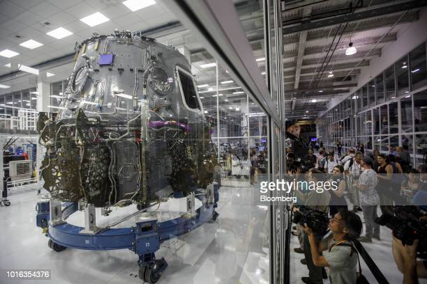 Attendees take pictures of the Crew Dragon spacecraft displayed in a clean room during the NASA Commercial Crew Program astronaut visit at the Space...